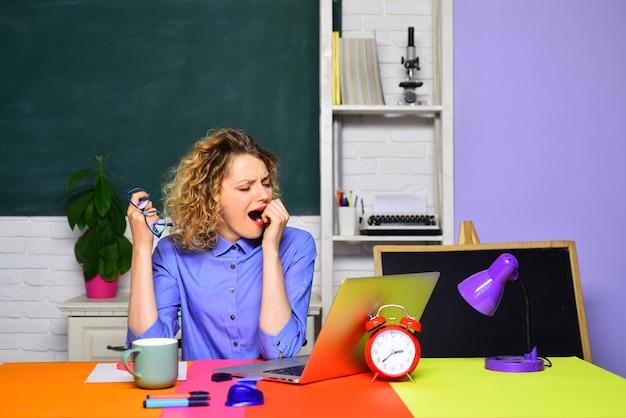 Tired teacher working with laptop in classroom hard work school job homework education concept world
