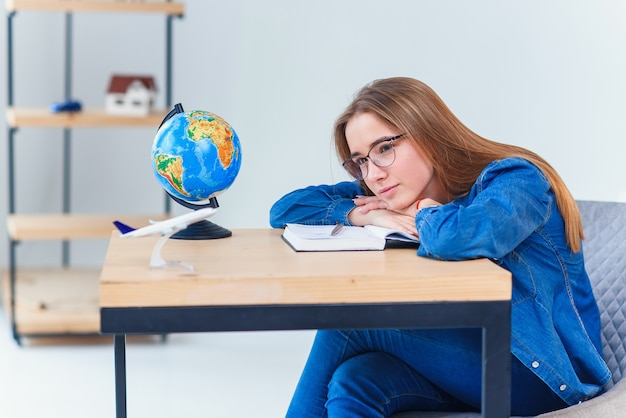 Уставшая девочка-подросток засыпает измученной после долгих часов обучения подготовке к экзамену. студентка колледжа спит за столом.