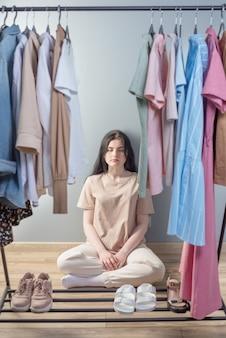服を着たハンガーで床に座っている疲れた10代の少女