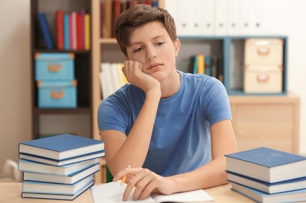 도서관에서 숙제를 하 고 피곤 된 십 대 소년