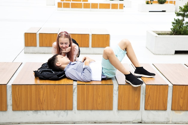 Tired teenager schoolboy sleeps after class in schoolyard of campus on wooden bench, schoolbag under his head. the girl looks at him in love. school love concept