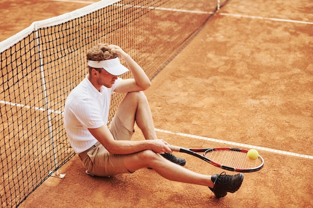 スポーツ服を着た疲れたテニス選手は、ネットに寄りかかって屋外のコートにいます。