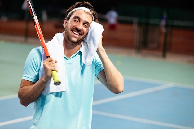 Усталый мужчина-теннисист на теннисном корте с ракеткой