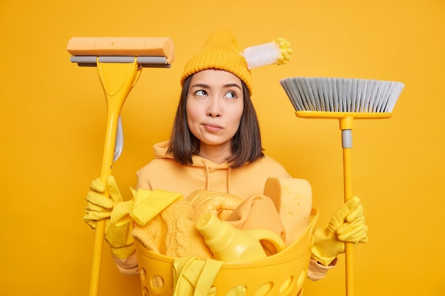 Tired thoughtful asian woman does laundry at home holds cleaning tools busy with cleanup going to sweep floor wash toilet wears hat sweatshirt and rubber gloves isolated over yellow background