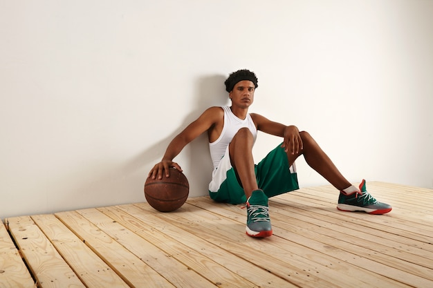 Tired and thoughtful black basketball player in green and white basketball outift sitting on light wooden floor resting his hand on a grunge brown basketball