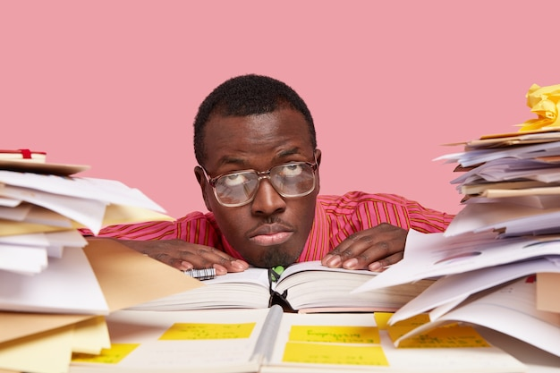Tired thoughtful dark skinned guy looks upwards, wears spectacles with thick lenses, keeps hands on opened diary, busy with studying paper documents
