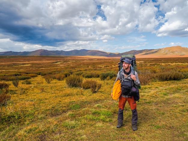 大きなバックパックとバッグを体の側面に持っている疲れた観光客は、ツンドラの山々を背景に、黒い劇的な雲を背景に遠くを喜んで見ています。