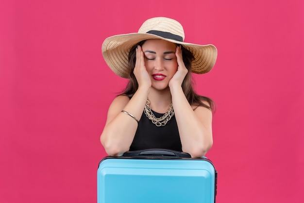 Ragazza giovane viaggiatore stanco che indossa maglietta nera in cappello mise le mani sulle guance su sfondo rosso