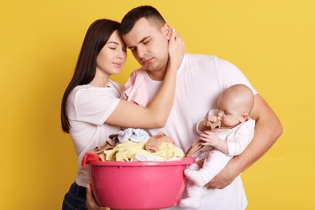 Усталые беспокойные родители, плачущие новорожденного и таз, полный чистой одежды, много домашней работы, позируют изолированно на желтой стене, влюбляются, сонные родители обнимаются и отдыхают минутку.