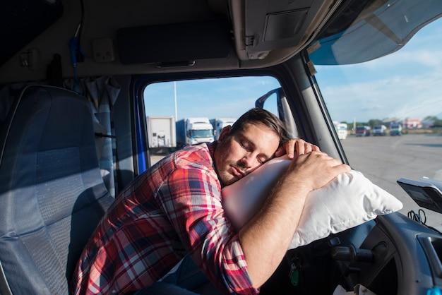 疲れたトラック運転手は彼の枕で寝ているハンドルに寄りかかった