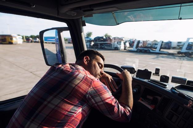 Усталый водитель грузовика спит в своей кабине