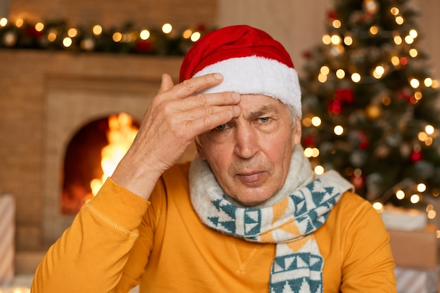 Tired unhappy annoyed old man being sick on christmas eve, suffering from headache, keeping hand on forehead, wearing yellow shirt and santa hat, with upset expression.