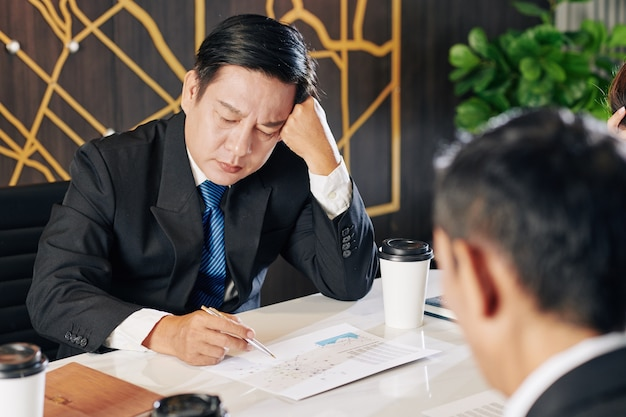 Tired unhappy businessman examining financial report after financial crisis