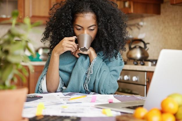 Giovane femmina afro-americana stanca e infelice che beve un'altra tazza di caffè