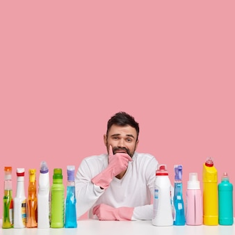 Tired unshaven guy holds chin, dressed in casual wear, sits at table with chemical cleaning detergents, washes everything, poses over pink wall with free space, looks unwillingly