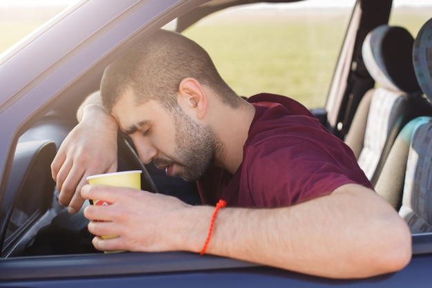 Tired unshaven male leans on wheel and holds paper cup of coffee