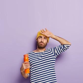 Uomo stanco con la barba lunga si asciuga il sudore sulla fronte, tiene la fiaschetta della bevanda calda, vestito con abiti casual a righe, sente la fatica dopo una lunga camminata