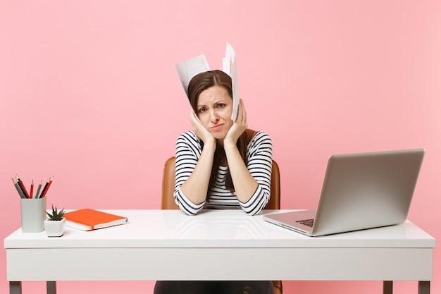 Усталая расстроенная женщина держит бумажные документы возле головы, опираясь на руки, работая над проектом, сидя в офисе с ноутбуком, изолированным на пастельно-розовом фоне. достижение бизнес-концепции карьеры. скопируйте пространство.