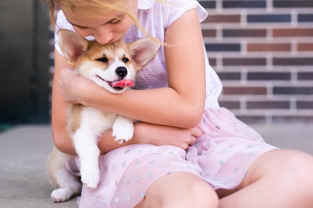 飼い主の足に横たわっている疲れたウェルシュコーギーペンブローク子犬。
