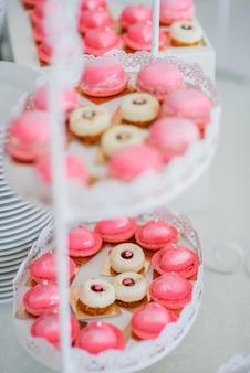 Утомленное белое блюдо с розовыми макаронами и вкусными белыми пирожными