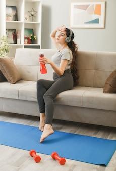 Stanco con gli occhi chiusi che mettono la mano sulla fronte giovane ragazza che indossa le cuffie con in mano una bottiglia d'acqua seduta sul divano nel soggiorno