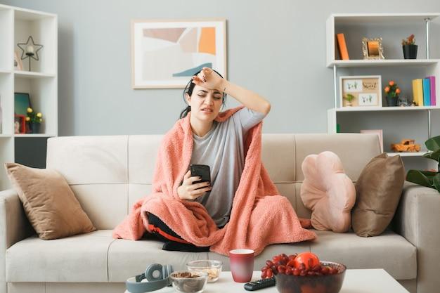 Усталая с закрытыми глазами, положив руку на лоб, молодая девушка, завернутая в плед, держит телефон, сидя на диване за журнальным столиком в гостиной