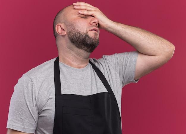 분홍색 벽에 고립 된 이마에 손을 넣어 제복을 입은 닫힌 눈 슬라브 중년 남성 이발사와 피곤