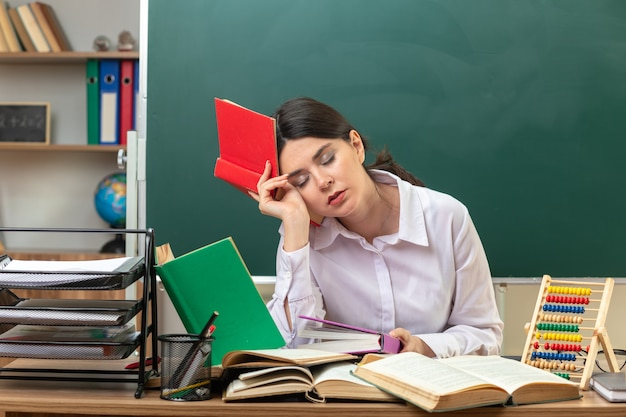 Tired with closed eyes young female teacher holding book around head sitting at table with school tools in classroom