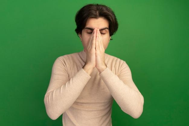 目を閉じて疲れた若いハンサムな男は緑の壁に隔離された手で鼻を覆った