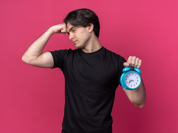 Stanco con gli occhi chiusi giovane bel ragazzo che indossa la maglietta nera che tiene sveglia mettendo il pugno sulla fronte isolato sul muro rosa