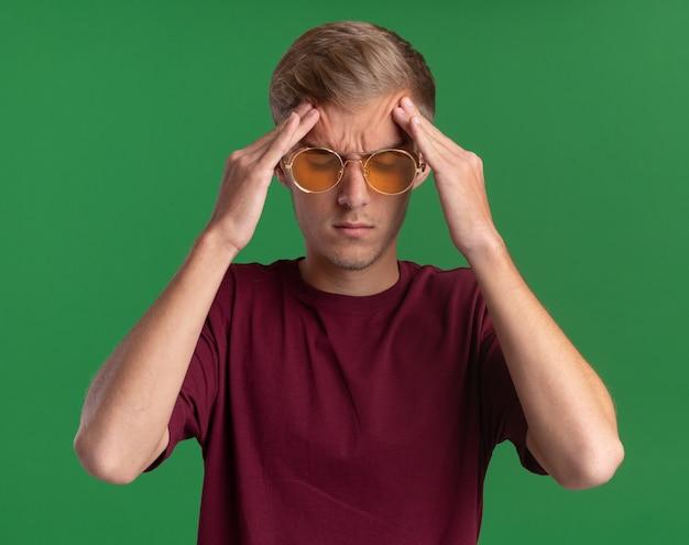 Усталый с закрытыми глазами молодой красивый парень в красной рубашке и очках, положив руки на лоб, изолированные на зеленой стене