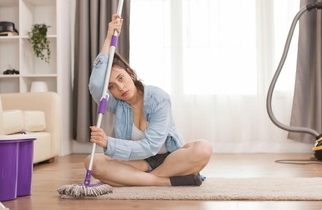 モップでアパートの床を掃除した後の疲れた女性
