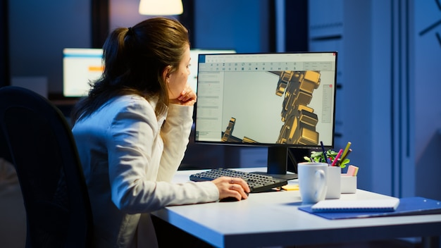 スタートアップオフィスの机に座って残業している現代のcadプログラムに取り組んでいる疲れた女性建築家。デバイスのディスプレイにcadソフトウェアを表示するpcでプロトタイプのアイデアを研究している産業の女性エンジニア