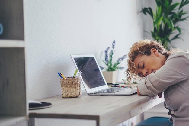 疲れた女性は、オフィスのワークステーションの部屋で自宅のフロントラップトップコンピューターで眠っています。過労活動のために眠っている成人女性。現代の病気のスマートワーキングコンセプト