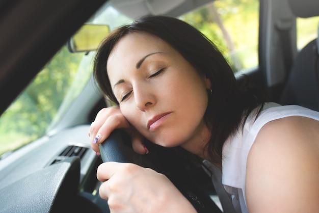 그녀의 차에서 운전대에 자 고 피곤 된 여자. 운전 안전 개념