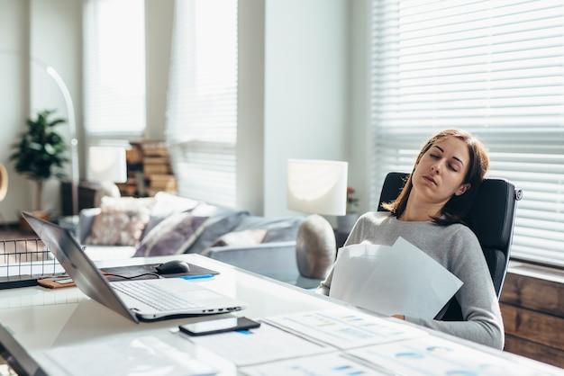 彼女の机で疲れた女性は仕事から休んでいます。