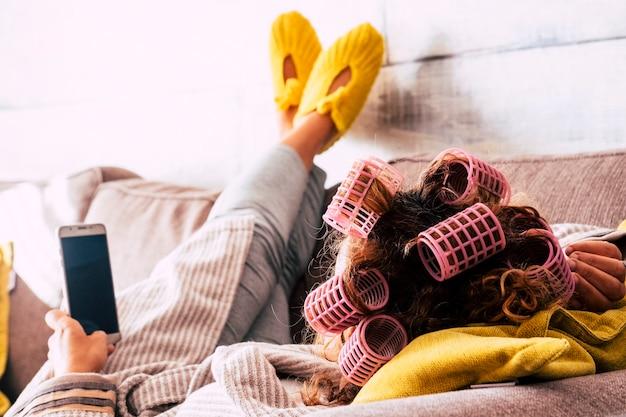 ソファに横になった携帯電話を使ってカーラーをしている家で疲れた女性