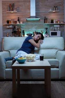 夜に映画を見ながら目を閉じて疲れた女性。自宅のリビングルームの居心地の良いソファに座ってテレビの前で寝ているパジャマ姿で疲れ果てた孤独な眠そうな主婦。