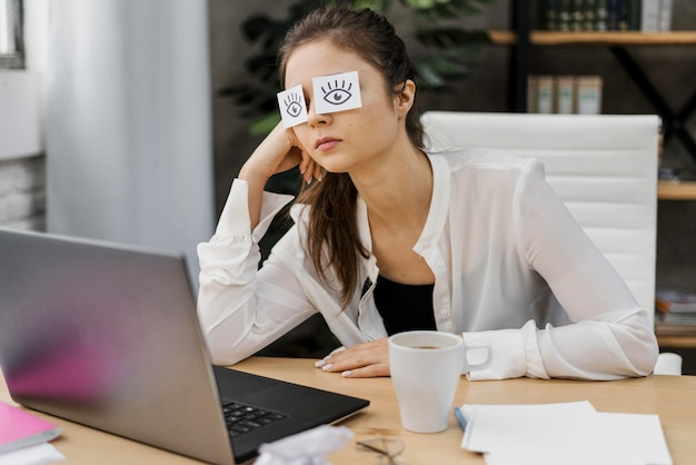 Tired woman covering her eyes with drawn eyes on paper