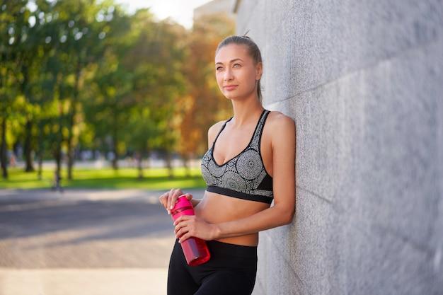 Усталая женщина пьет воду после утренней тренировки молодая спортивная женщина стоит, опираясь на поверхность парка уолл-сити-стрит после бега. концепция здорового образа жизни копирование пространства