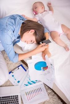 疲れた女性が自宅で仕事をしながら眠りに落ちる。