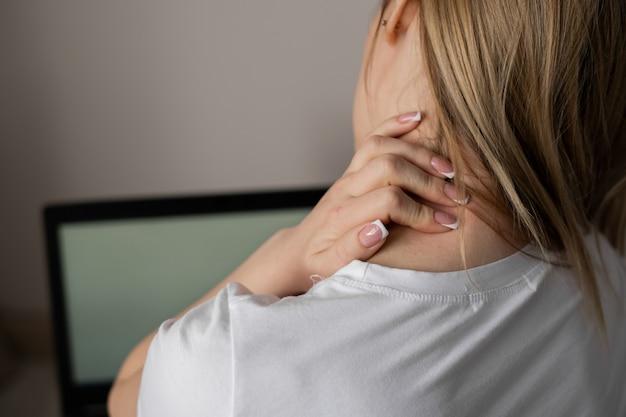 首の痛みを感じ、緊張した筋肉をマッサージし、慢性的な肩の背中の痛みに苦しんでいる疲れた女性