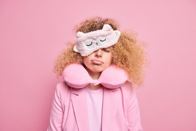 Tired woman feels exhausted after long journey tries to have nap while traveling has sleepy expression wears sleepmask and travel pillow around neck dressed formally isolated on pink wall