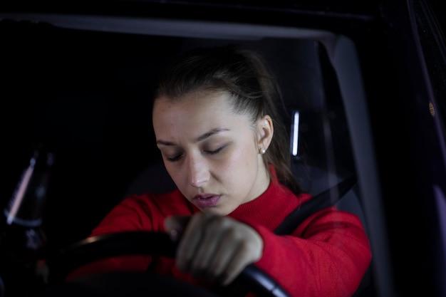 Усталая женщина заснула, сидя в машине