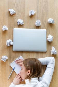 Утомленный фрилансер женщины спать и отдыхая ее голова на тетради на таблице, пишущ на блокноте, скомканных шариках бумаги и компьтер-книжке вокруг, взгляд сверху.