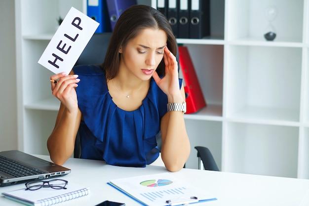 Утомленная женщина имеет проблемы на работе, вешает записку с сообщением «помощь»