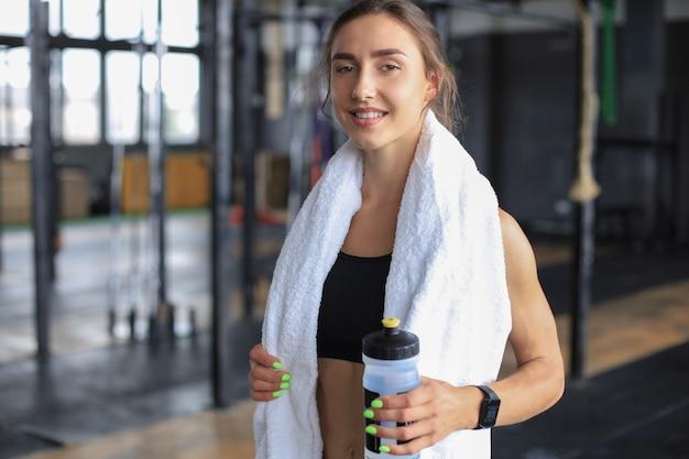 운동 후 휴식을 취하는 피곤한 여자. 그녀의 목에 수건으로 체육관에서 지친 여성 운동 선수.
