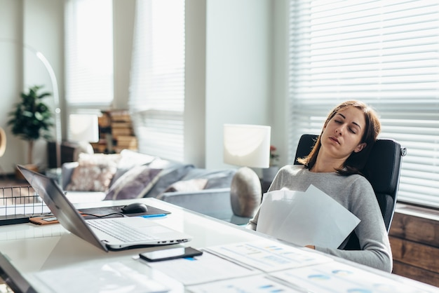 Tired woman at her desk is resting from work.
