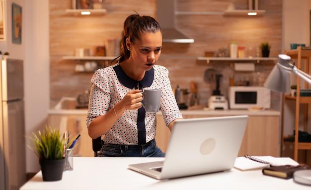 ノートパソコンで作業しながら夜遅くにキッチンでコーヒーを保持している疲れた女性。深夜に最新のテクノロジーを使用して、仕事、ビジネス、忙しい、キャリア、ネットワーク、ライフスタイルのために残業している従業員。