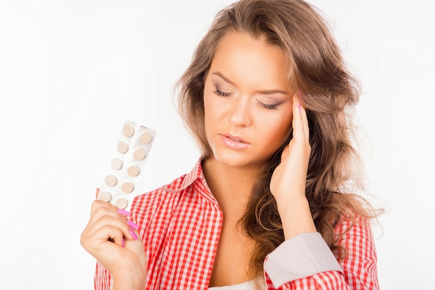Tired woman holding tablets and suffering from headache